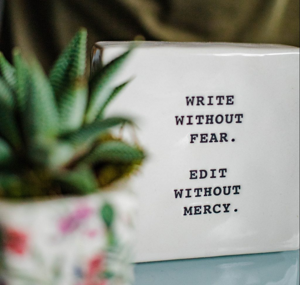 "A printed block reads ""Write without fear. Edit without mercy."""